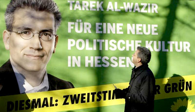 Tarek Al-Wazir, party leader of German green party Buendnis90/Die Gruenen in the German state of Hesse poses in front of an election campaign placard in Wiesbaden December 29, 2008. Al-Wazir will start as green party's top candidate for the upcoming state elections in Hesse, January 18. Slogan on the placard reads 'For a new political culture in Hesse'